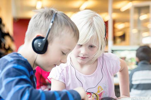 To børn lytter med høretelefoner på