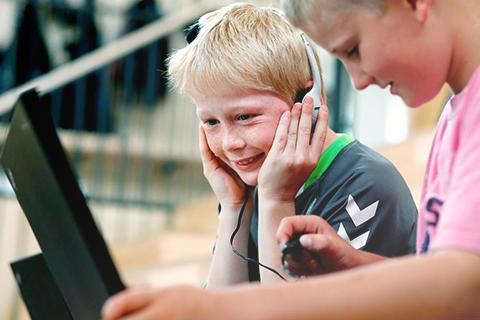 Elev har høretelefoner på og kigger på computer
