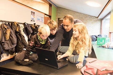 Tre grundskoleelever undervises af en lærer