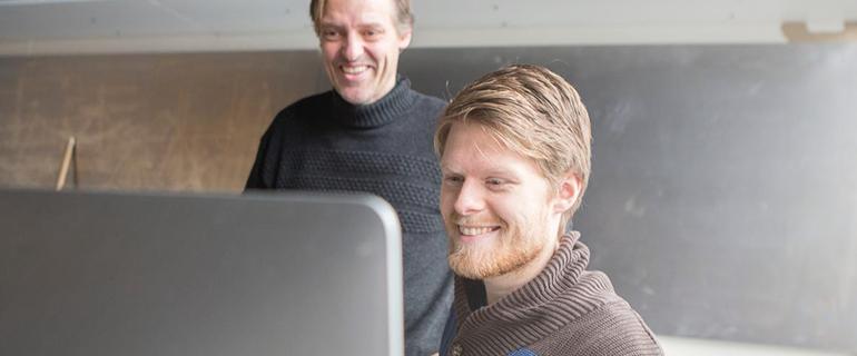 To mænd kigger på en computerskærm