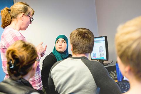 Lærer hjælper elever med gruppearbejde