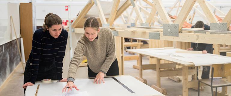 To elever i snedkerlokale arbejder ved et bord