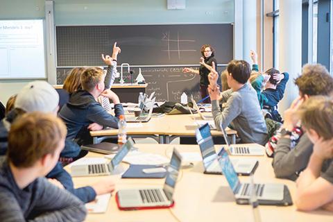 Elever rækker hånden i vejret til klasseundervisning
