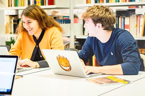 To elever sidder og arbejder på computer