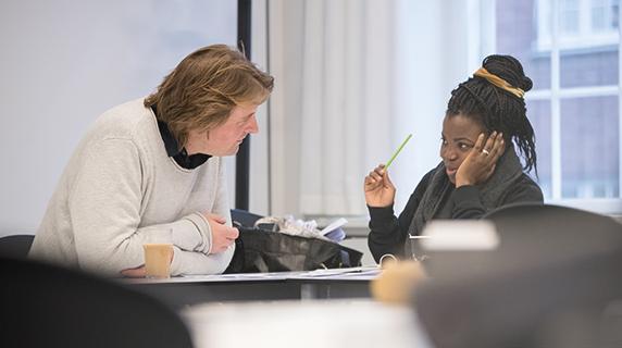 To voksne elever i et klasselokale taler sammen