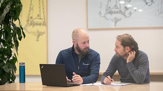 To voksne elever taler sammen ved en computer